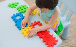 Criança pré-escolar 3 anos que jogam com blocos coloridos do brinquedo Imagens de Stock