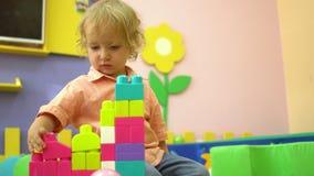 Criança pré-escolar bonito loura que joga com multi blocos de apartamentos coloridos no infantário Desenvolvimento infantil dentr video estoque