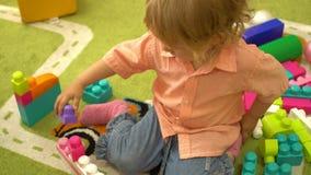 Criança pré-escolar bonito que joga com multi blocos de apartamentos coloridos no jardim de infância Educação no infantário video estoque
