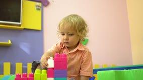 Criança pré-escolar loura bonita que joga com multi blocos de apartamentos coloridos no jardim de infância Desenvolvimento infant vídeos de arquivo