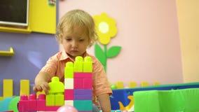 Criança pré-escolar loura que joga com multi blocos de apartamentos coloridos no infantário Desenvolvimento infantil dentro vídeos de arquivo