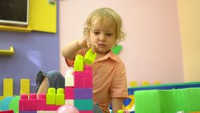 Criança pré-escolar loura que joga com multi blocos de apartamentos coloridos no jardim de infância Desenvolvimento infantil no b video estoque