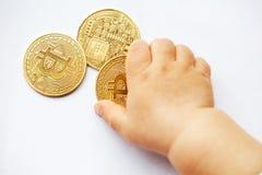 A criança puxa as mãos para moedas do cryptocurrency de Bitcoin O futuro é sistemas descentralizados Close-up fotografia de stock