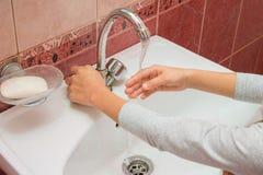 A criança quadro a mão sob o córrego da água fria Fotos de Stock Royalty Free