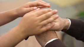 Criança que afaga as mãos do ancião, programa de apoio social para pensionista, bondade video estoque