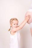 Criança que alcanga a barriga grávida Foto de Stock Royalty Free