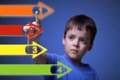 Criança que aponta às setas coloridas Imagens de Stock