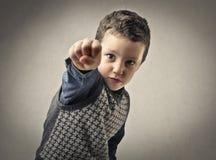 Criança que aponta com seu punho imagem de stock