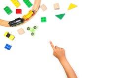 Criança que aponta o dedo aos brinquedos coloridos Girador da inquietação, carros, trem do brinquedo, tijolos e blocos no fundo b foto de stock