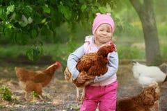 Criança que aprecia guardando a galinha em seus braços