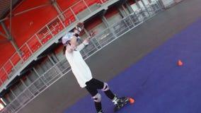 Criança que aprecia no parque da patinagem de rolo filme