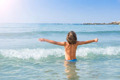 Criança que aprecia o sol e as ondas Fotografia de Stock Royalty Free