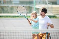 Criança que aprende jogar o tênis com seu pai na corte exterior Menina com raquete de tênis fotografia de stock royalty free