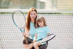 Criança que aprende jogar o tênis com sua mãe na corte exterior Menina com raquete de tênis imagem de stock royalty free