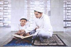 Criança que aprende ler o Corão com pai Fotografia de Stock Royalty Free