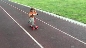 Criança que aprende montar um 'trotinette' no estádio video estoque