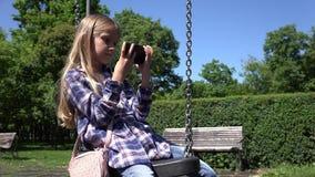 Criança que balança jogando a tabuleta, criança exterior na menina do parque em usos Smartphone do balanço filme