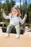 Criança que balança no parque urbano Fotos de Stock