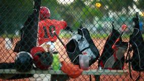 Criança que balança seu bastão de beisebol Sacos e capacetes vistos da cerca de trás no campo filme