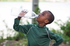 Criança que bebe a água engarrafada na natureza foto de stock