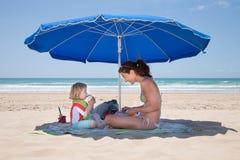 Criança que bebe do bloco com a mãe na praia Imagens de Stock Royalty Free