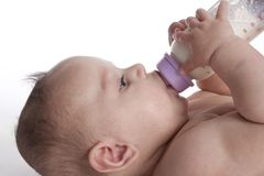 Criança que bebe do frasco de bebê Imagens de Stock Royalty Free