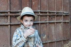 Criança que bebe um vidro do leite fresco Fotografia de Stock Royalty Free