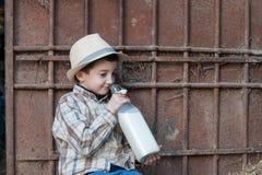 Criança que bebe uma garrafa do leite fresco Fotografia de Stock Royalty Free