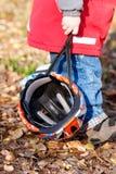 Criança que carreg seu capacete de ciclagem Fotografia de Stock