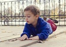Criança que coloca na parte externa à terra foto de stock