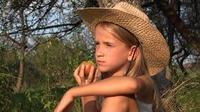 Criança que come Apple na jarda na vila, fazendeiro Girl no pomar que prova os frutos 4K video estoque
