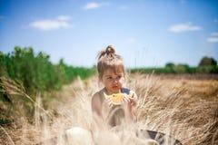 Criança que come a fatia de melancia amarela em um campo Fotos de Stock