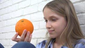 Criança que come frutos das laranjas no café da manhã, criança da menina que cheira a cozinha saudável do alimento filme