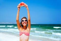 Criança que come a melancia na praia imagens de stock