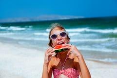 Criança que come a melancia na praia fotografia de stock