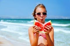 Criança que come a melancia na praia fotos de stock