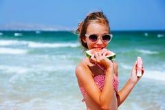 Criança que come a melancia na praia foto de stock