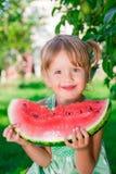 Criança que come a melancia no parque nas horas de verão aprecíe Retrato Menina feliz Foto de Stock