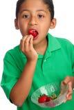 Criança que come morangos Fotos de Stock
