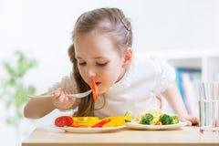 Criança que come o alimento saudável em casa Fotografia de Stock Royalty Free