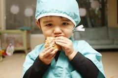 Criança que come o bolinho Fotografia de Stock