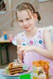 Criança que come o bolo de aniversário - fundo real natural fotografia de stock