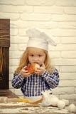 Criança que come o bolo do pão na parede de tijolo branca imagem de stock