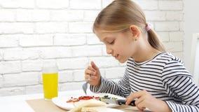 A criança que come o café da manhã na cozinha, criança come ovos saudáveis do alimento, vegetais da menina video estoque