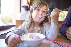 Criança que come o gelado da bacia no restaurante Fotos de Stock
