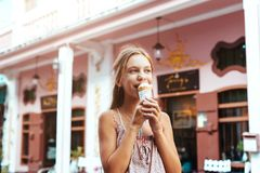 Criança que come o gelado na rua da cidade Imagens de Stock Royalty Free