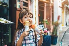 Criança que come o gelado na rua da cidade Fotografia de Stock