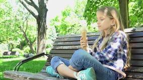 Criança que come o gelado no campo de jogos, assento de relaxamento da menina no banco no parque 4K filme