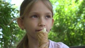 Criança que come o gelado no campo de jogos, assento de relaxamento da menina no banco no parque 4K vídeos de arquivo