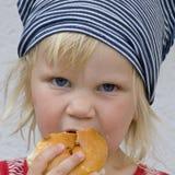 Criança que come o rolo de pão Fotografia de Stock Royalty Free